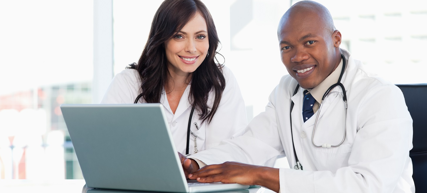 Medical staff working in front of a grey laptop while sitting at the desk